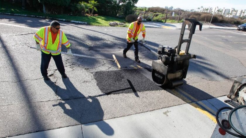 D'Arcy Harris (right) and Jose Nunez, who repair pot holes for the City of San Diego, work at Olney Street and Pacific Beach Drive on Thursday in the Pacific Beach area of San Diego, California.