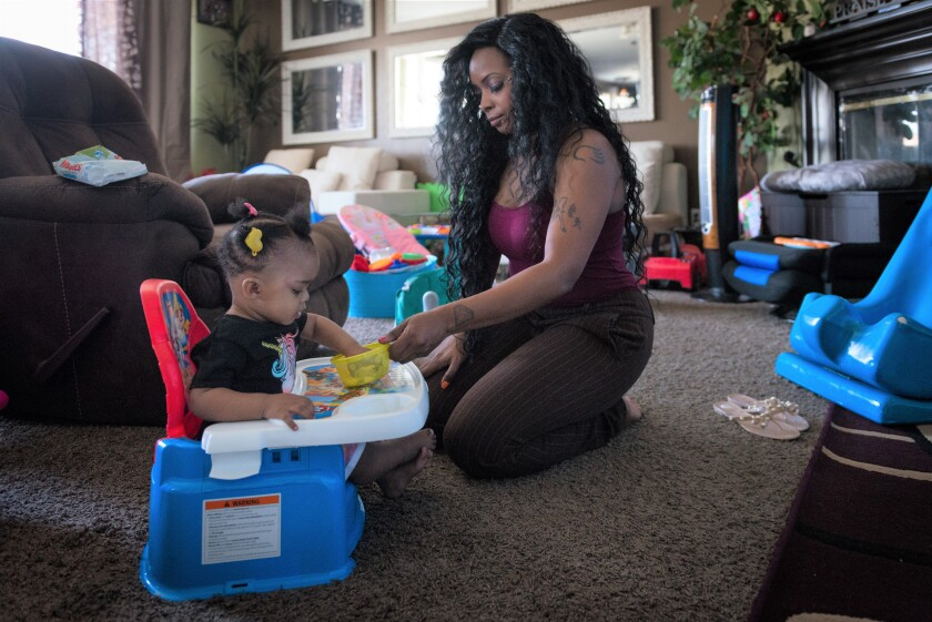 Denise Williams, of Adelanto, cares for her 1-year-old daughter Gigi Williams.