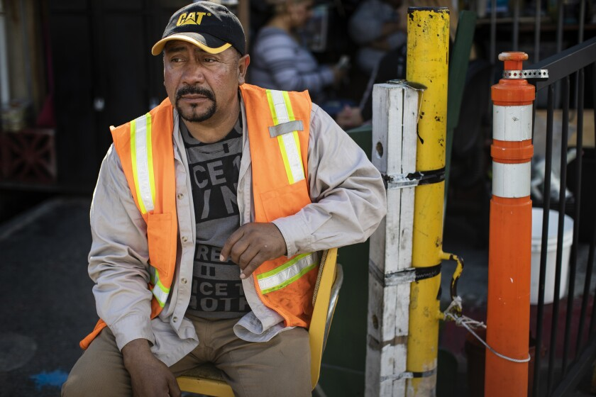 Jose Hernandez, jobs coordinator for the day laborers, waits in the Home Depot parking lot for work