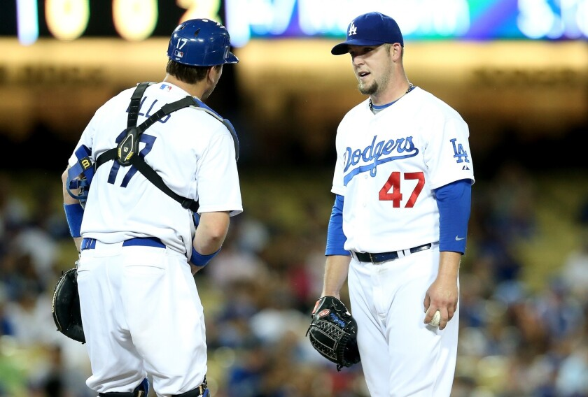 Dodgers pitcher Paul Maholm, right, talks with catcher A.J. Ellis in the fourth inning. Maholm gave up 10 runs, five earned, in the Dodgers' 13-3 loss to the Marlins.
