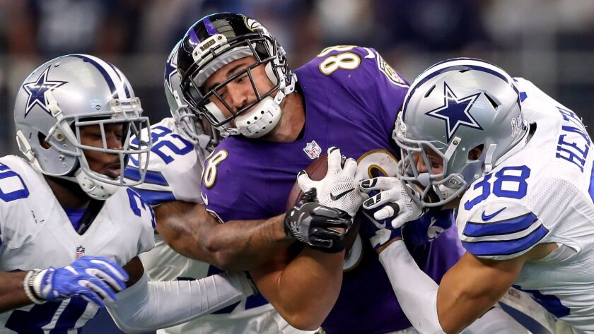 Baltimore Ravens tight end Dennis Pitta, center, is brought down by Dallas Cowboys safety Jeff Heath
