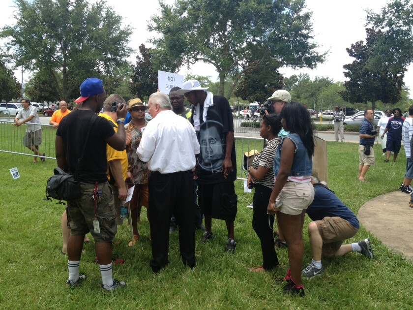 Casey Kole, center in white shirt, has watched the George Zimmerman case unfold on TV and believes he is innocent. Outside the courthouse on Saturday he talks with a group of Trayvon Martin supporters.
