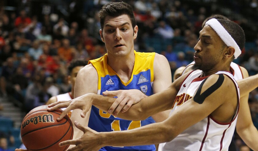 UCLA forward Gyorgy Goloman, left, and USC guard Jordan McLaughlin battle for the ball during the second half in the first round of the Pac-12 men's tournament on Wednesday in Las Vegas.