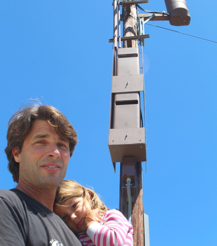 Peter Venieris poses with his daughter Grace, 3, in front of a 5G tower recently installed in front of their La Jolla home.