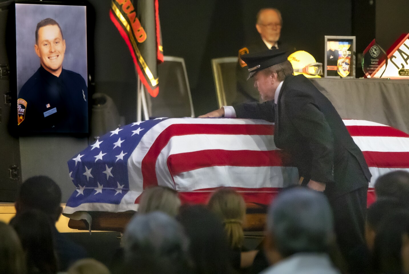 Igor Katkov, the father of Cal Fire Firefighter Yaroslav Katkov, wearing his son's uniform hat, places his hand on his son's flag draped casket during the celebration of life for Yaroslav, August 6, 2019, at North Coast Church in Vista, California. He passed away July 29 after suffering a medical emergency while on a training hike with other firefighters near Cal Fire San Diego County Fire Station 16 in De Luz, where he was assigned. He had been with Cal Fire for less than a year.