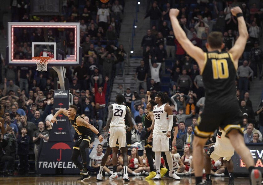 Wichita State's Dexter Dennis, left and teammate Wichita State's Erik Stevenson, far right react at the end of a double overtime an NCAA college basketball game against Connecticut, Sunday, Jan. 12, 2020, in Hartford, Conn. (AP Photo/Jessica Hill)