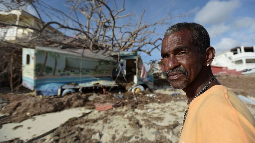 Juan Antonio Higuey shows his destroyed home at Cold Bay community after the passage of Hurricane Ir
