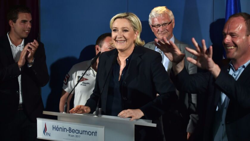 France's far-right National Front leader and parliamentary candidate Marine Le Pen, center, speaks i