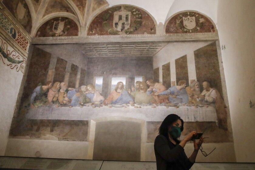 A visitor takes a selfie as she admires Leonardo da Vinci's mural painting ' The Last Supper ', dating back to 1495-1498 and preserved at the ex-Renaissance refectory of the convent adjacent to the sanctuary of Santa Maria delle Grazie church, in Milan, Italy, Wednesday, June 10, 2020. 'Last Supper' reopened Tuesday after three months of closure due to COVID-19 lockdown measures. (AP Photo/Luca Bruno)