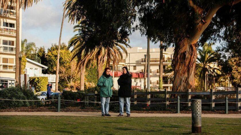 Dos personas usan chaquetas y orejeras mientras el sol se pone en Palisades Park en Santa Monica. Las temperaturas llegaron a mediados de los 60 el domingo y se espera que bajen abruptamente esta semana. (Maria Alejandra Cardona / Los Angeles Times)