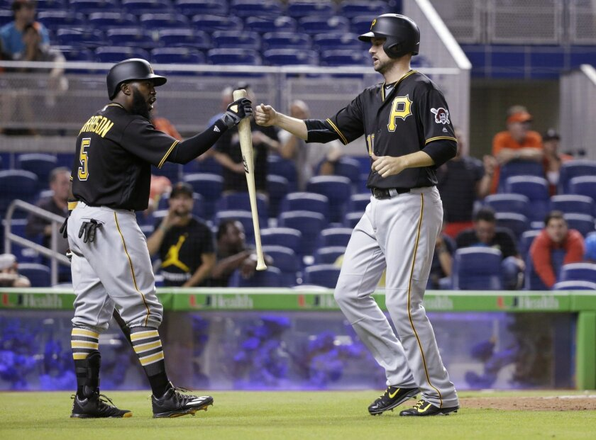 Pittsburgh Pirates' Jordy Mercer, right, is congratulated by Josh Harrison (5) after Mercer scored on a single by John Jaso during the ninth inning of a baseball game against the Miami Marlins, Thursday, June 2, 2016, in Miami. The Marlins defeated the Pirates 4-3 in 12 innings. (AP Photo/Wilfredo
