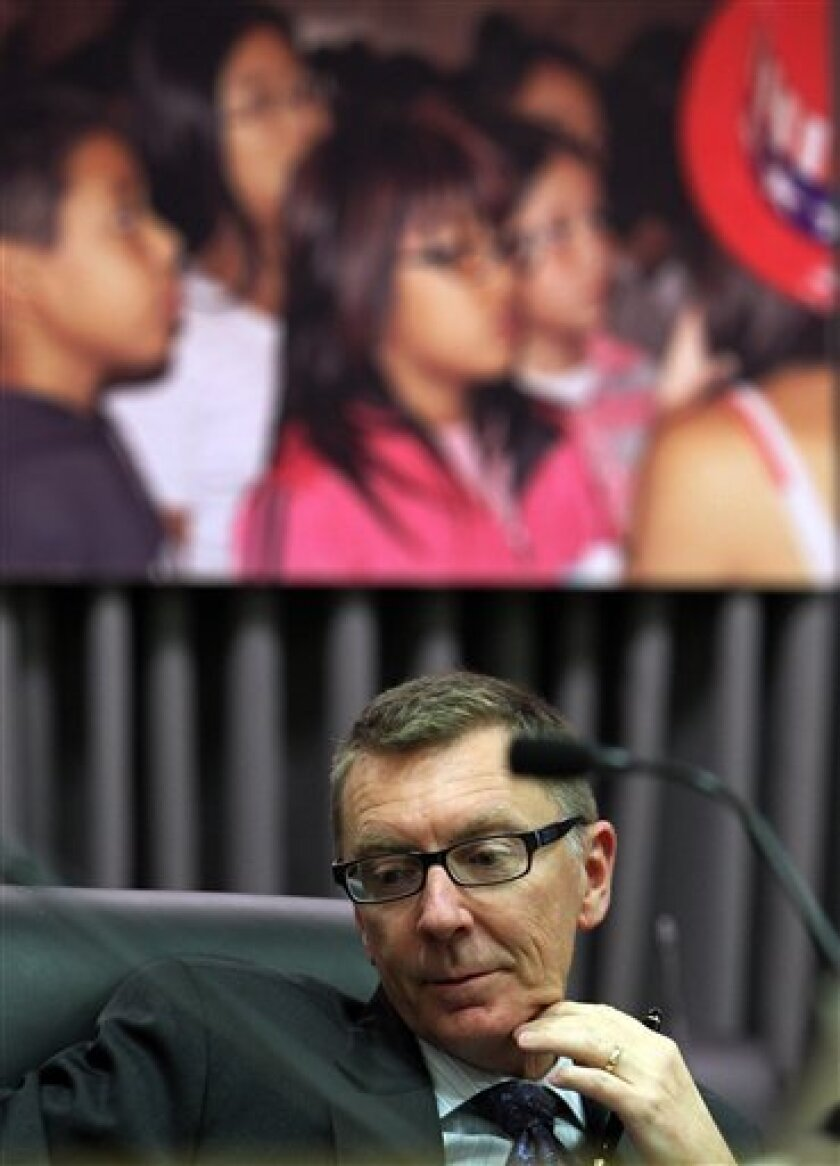 With portraits of school children behind him, Los Angeles Unified School District Superintendent John Deasy takes his seat following a closed-door meeting of the Board of Education in downtown Los Angeles Tuesday, Feb. 7, 2012. Prosecutors have filed a lewd-acts complaint against the second of two teachers removed from a Los Angeles-area elementary school, and the Board voted to fire him in the closed-door meeting. On Monday night Deasy said that more than 120 staff members at Miramonte Elementary School — everyone from the principal and teachers to the cafeteria workers — were being replaced because a full investigation of the allegations will be disruptive and staffers will require support to get through the scandal. (AP Photo/Reed Saxon)
