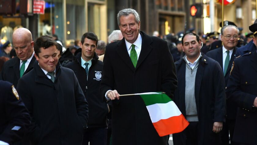 Mayor Bill de Blasio carries an Irish flag while marching in the annual St. Patrick's Day parade Saturday in New York City.