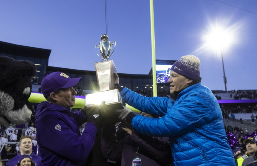 Washington Governor Jay Inslee hands Washington head coach Chris Petersen the Apple Cup after an NCAA college football game between Washington and Washington State, on Friday, Nov. 29, 2019 in Seattle. Washington won 31-13. (AP Photo/Stephen Brashear)