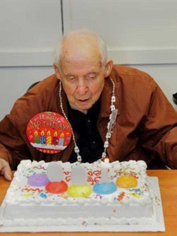 Centenarian Ernie Fowler blows out his birthday candles.