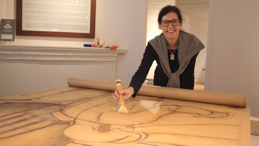 Janet Ruggles, paper conservation chief director at Balboa Art Conservation Center, dusts off one of