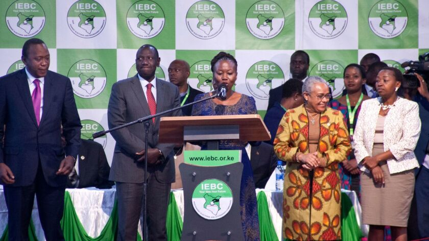 Kenyan electoral official Roselyn Akombe, center, speaks as President Uhuru Kenyatta, left, prepares to receive his electoral win certificate, later nullified in Nairobi, Kenya. Akombe resigned Oct. 18 and fled the country after receiving threats.
