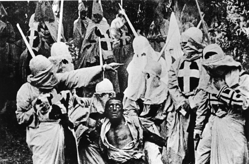 """Actors costumed in the full regalia of the Ku Klux Klan chase down a white actor in blackface in a still from """"The Birth of a Nation."""""""