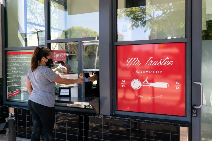 A customer get a treat from Mr. Trustee, a ice cream shop and takeout window by the Trust Restaurant Group in Mission Hills