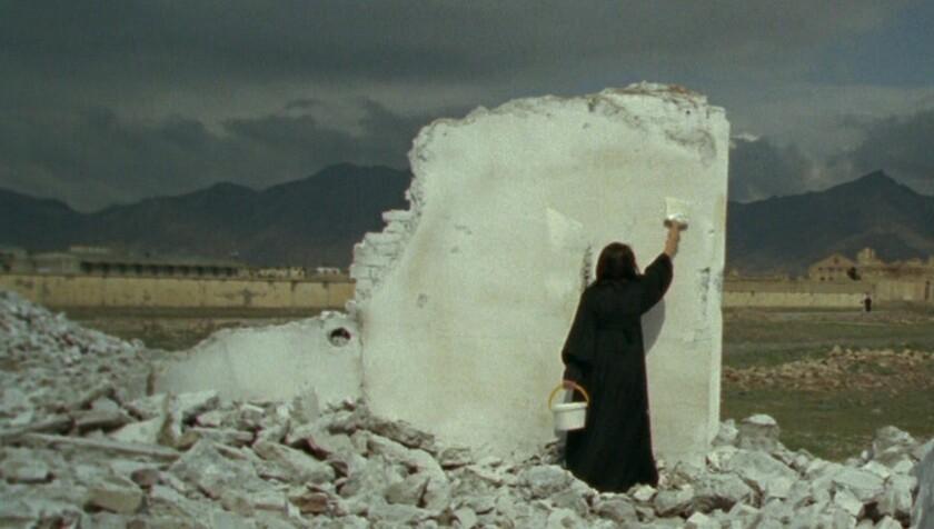 ویدئو هنوز زنی را با لباس سیاه نشان می دهد که روی توده ای از آوار ایستاده است و قطعه ای از دیوار را به رنگ سفید نقاشی می کند.