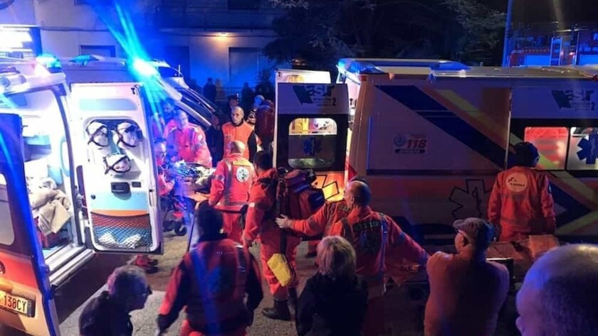 Rescuers help the injured outside a disco in Corinaldo, Italy, early Saturday.
