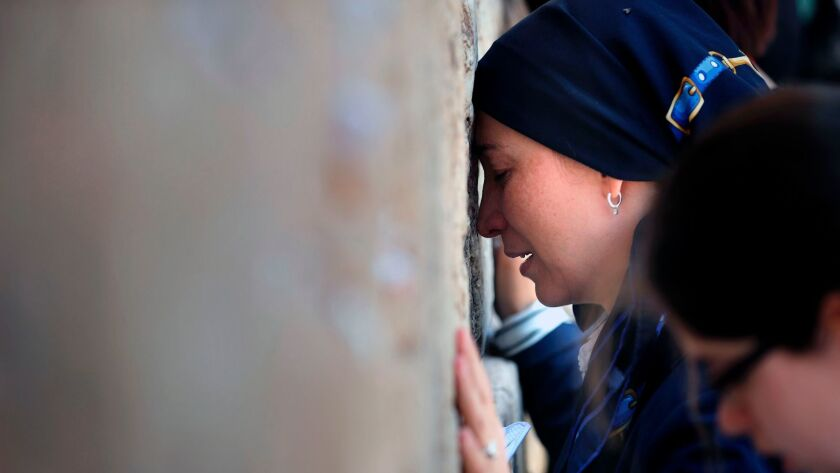 Jewish women pray at the men's section of the Western Wall in Jerusalem's Old City. Israel is shelving a deal to allow men and women to pray together at the Western Wall.