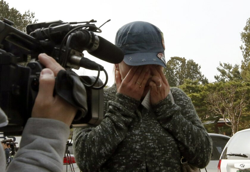 A representative of sex workers wipes her tears after listening to a judgment at the Constitutional Court in Seoul, South Korea, Thursday, March 31, 2016. South Korea's constitutional court on Thursday upheld laws that toughened punishment on prostitutes, pimps and their clients. he 2004 legislation drove thousands of sex workers in traditional red-light zones out of business in South Korea, but prostitution has still thrived in the shadows. (AP Photo/Lee Jin-man)