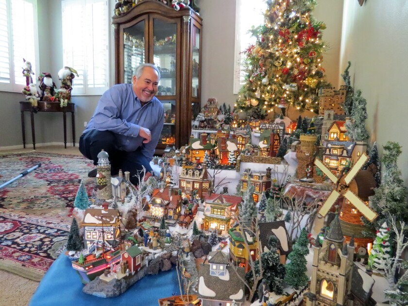 Mike Kompanik, 64, admires his enormous illuminated Victorian village holiday display in the den of his Scripps Ranch home on Dec. 13. Kompanik, a retired Navy captain, has been building his collection over the past 34 years.