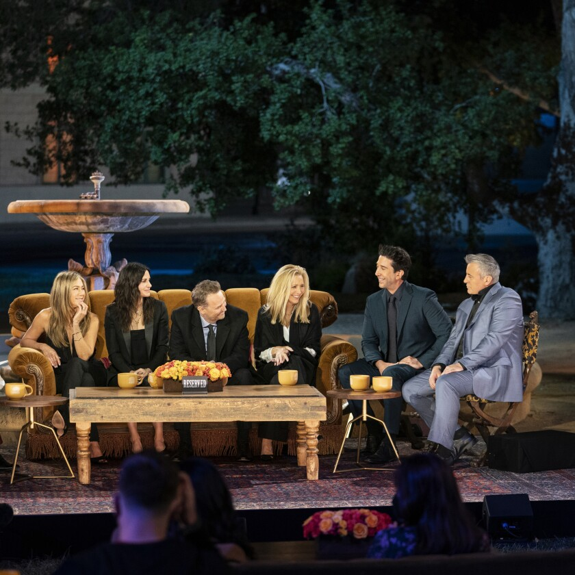 """""""Friends"""" cast members sit on a couch and chairs in front of a fountain."""