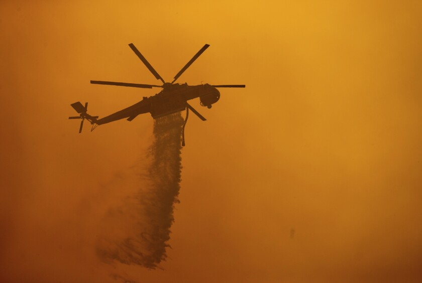 A helicopter drops water on the Fawn fire.