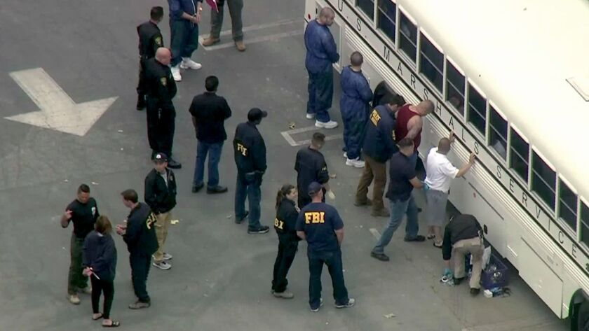 Federal law enforcement officials search suspects arrested during Operation Dirty Thirds, where they