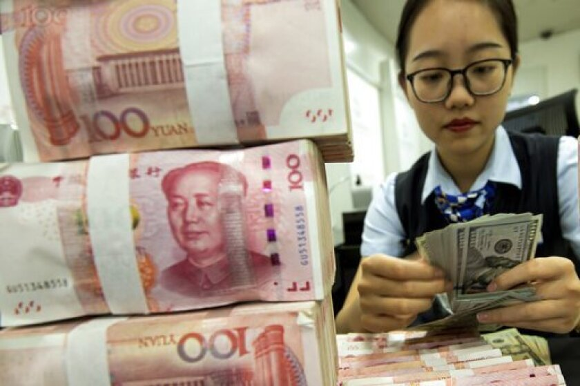 A bank employee counts U.S. dollars next to stacks of Chinese yuan at a bank outlet in Hai'an in eastern China's Jiangsu province.