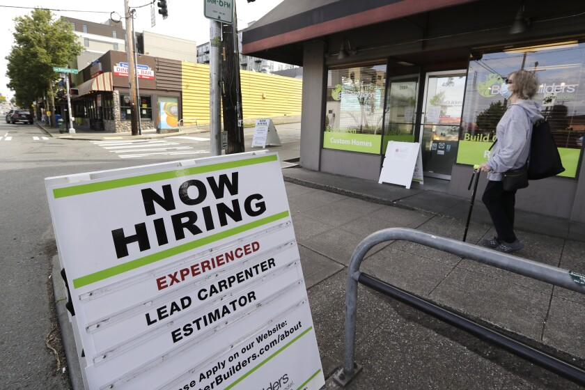 A pedestrian wearing a mask walks past a board advertising a job opening for a remodeling company June 4 in Seattle.