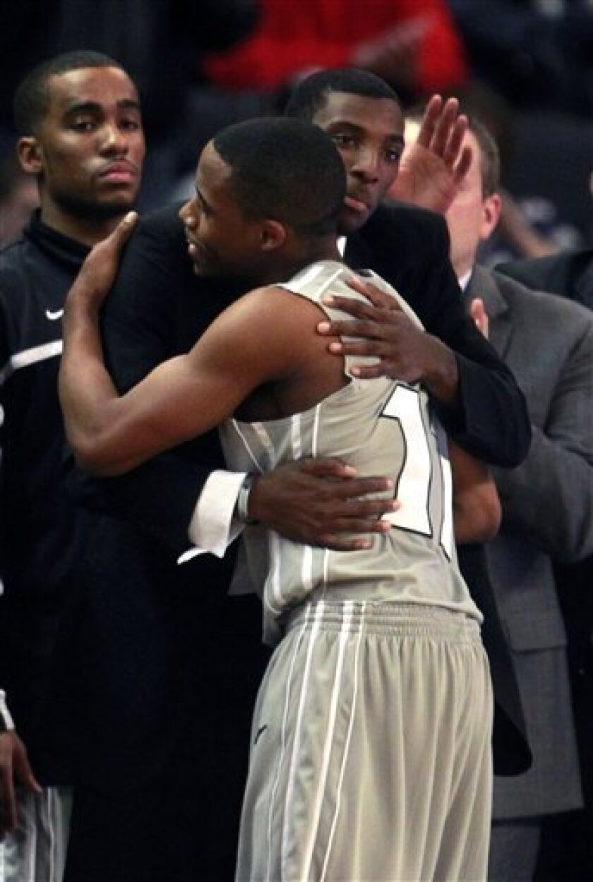 Providence's Bryce Cotton, center front, receives a hug from teammate Gerard Coleman, behind center, moments before the end of an NCAA college basketball game against Louisville in Providence, R.I., Tuesday, Jan. 10, 2012. Cotton scored 27 points in the game to help Providence defeat Louisville 90-59. (AP Photo/Steven Senne)