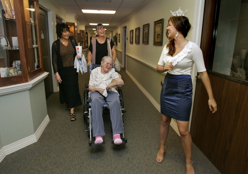 At the Silverado Senior Living facility Miss California Arianna Afsar greets resident Bonnie Graham with her daughters Barb Rodeman, of Indiana, at left, and Susan Barrett, or Arizona, at right, as she's on her way to perform for the facility's residents and clients of the Glenner Alzheimer's Cente