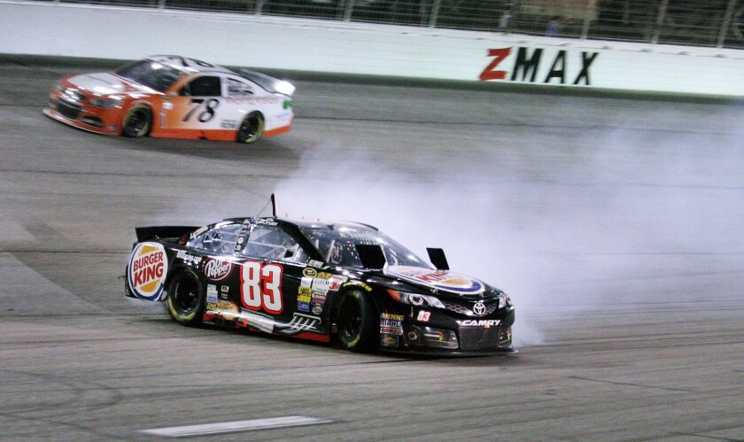 Sprint Cup Series driver Ryan Truex (83) slides in a turn during an NASCAR Sprint Cup auto race at Atlanta Motor Speedway Sunday, Aug. 31, 2014, in Hampton, Ga. Sprint Cup Series driver Martin Truex Jr. (78) dives past in the background. (AP Photo/Dale Davis)