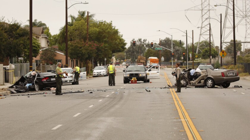 Los Angeles County Sheriff's deputies take measurements at the scene of a fatal collision in Pico Rivera early Monday.