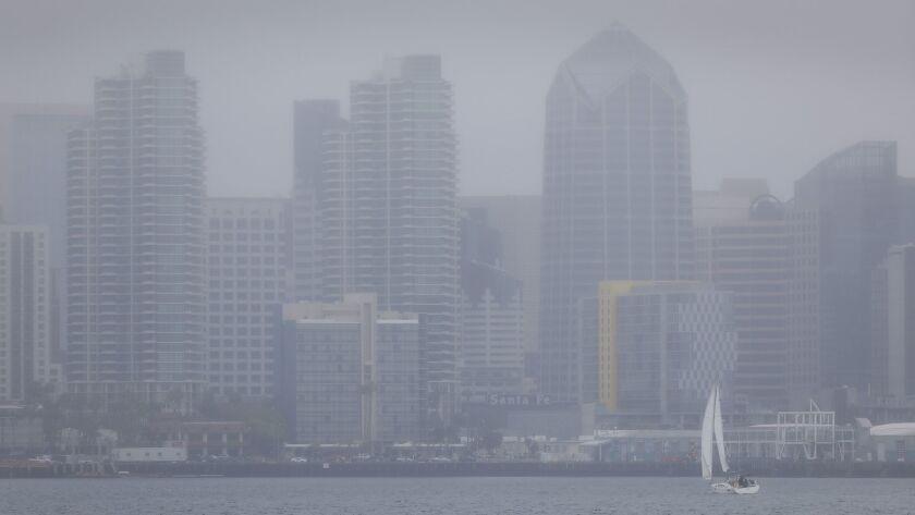 With the San Diego downtown skyline partially shrouded in fog Thursday afternoon, a sailboat makes its way through San Diego Bay. Thursday was a gray day downtown, with plenty of fog and mist but not too much rain through late afternoon.