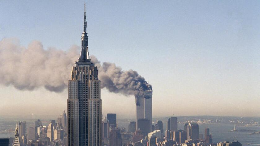 The twin towers of the World Trade Center burn behind the Empire State Building in New York on Sept. 11, 2001. (Associated Press)