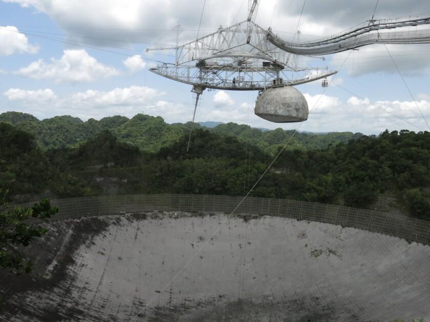 Esta imagen, tomada el 13 de julio de 2016, muestra el mayor radiotelescopio del mundo en el observatorio Arecibo en Arecibo, Puerto Rico. La retirada de fondos del gobierno de Estados Unidos y la construcción de otros telescopios más grandes y potentes en lugares como China o Chile amenazan la existencia de este. (AP Foto/Danica Coto)