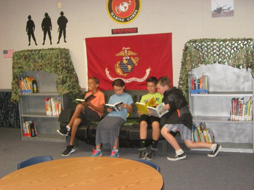 """Students relax in the """"jeep"""" couch at the military-themed Ben Carson Reading Room at Bonsall West Elementary School. The Carson Scholars Fund donated $15,000 for books and materials to refurbish a portable classroom to encourage leisure reading."""