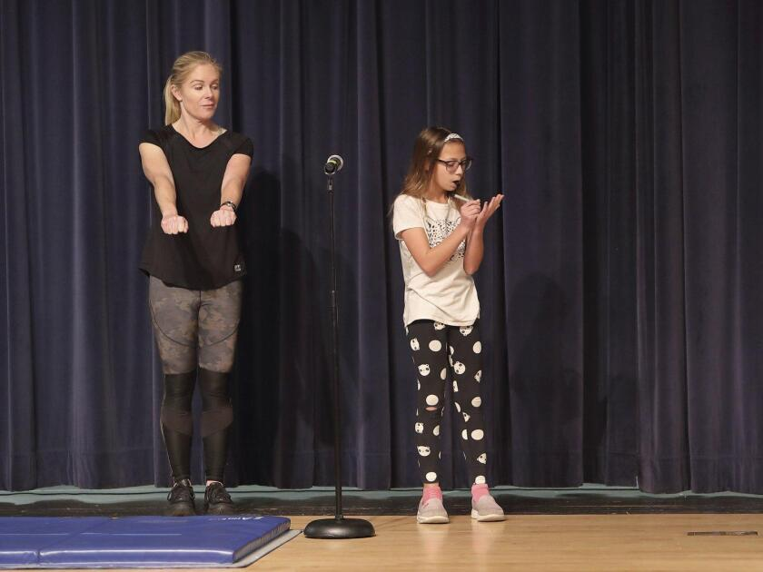 """""""The Amazing Starlight"""" (Portia Perry, right) performs a magic trick with the help of an audience member"""