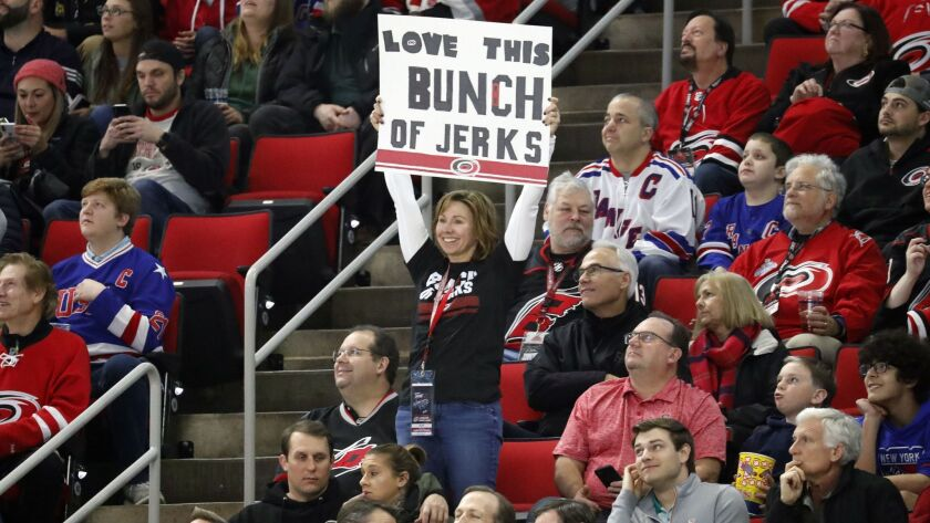 """A Carolina Hurricanes fan holds a sign saying she loves this """"Bunch of Jerks,"""" a reference to the te"""