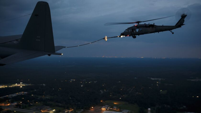 A military search and rescue helicopter refuels midflight before resuming nighttime missions over in