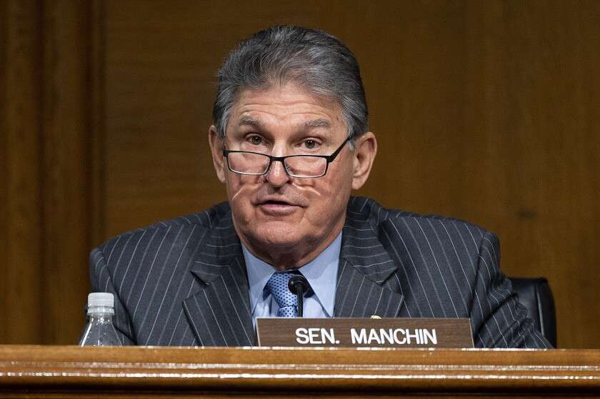 A man in a suit and glasses is seated behind a sign that reads Sen. Manchin