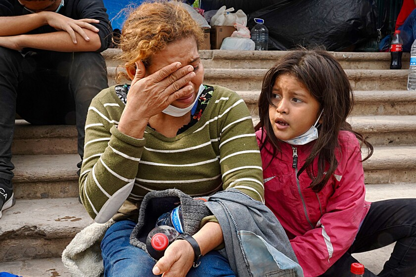 A woman with her hand over her face and a child sit on steps