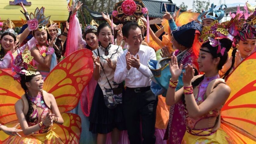 Wanda Group Chairman Wang Jianlin mingles with performers at Hefei Wanda Culture Tourism City in Hefei, in east China's Anhui province, in September.