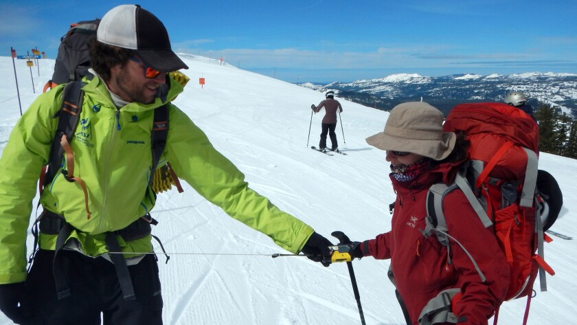 Alpine Skills International guide Jacob Swarz checking Jessica Hays'€™ avalanche beacon before setting out with a group on an overnight backcountry ski traverse from the Sugar Bowl to Squaw Valley ski resorts on the northwest side of Lake Tahoe.