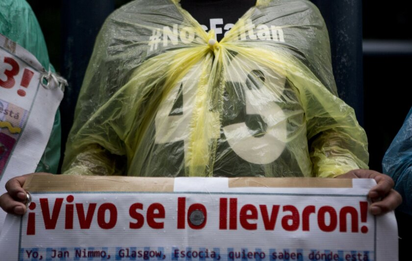 """FILE - In this May 26, 2016, file photo, a relative carries signs that reads in Spanish """"They took them alive!"""" referring to the 43 missing students from a rural teachers college during a march in Mexico City, Thursday. Mexico's National Human Rights Commission said Monday, July 11, that a classmat"""