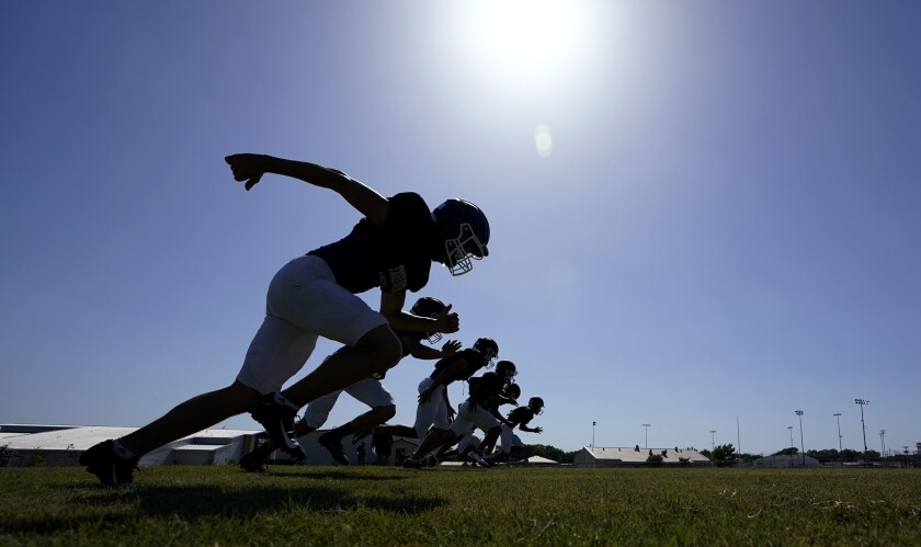 Thrall High School football players, wearing face masks at all times and using social distancing when possible, go through a practice, Thursday, Aug. 13, 2020, in Thrall, Texas. Texas will play high school football this fall, but some of it will be delayed, fans will be limited and masks will be required as the state continues to fight a surge in new coronavirus cases. (AP Photo/Eric Gay)